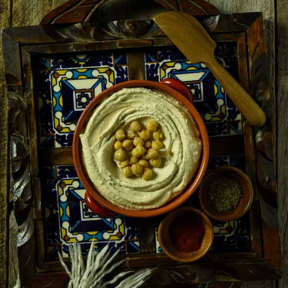hummus in bowl topped with chickpeas.