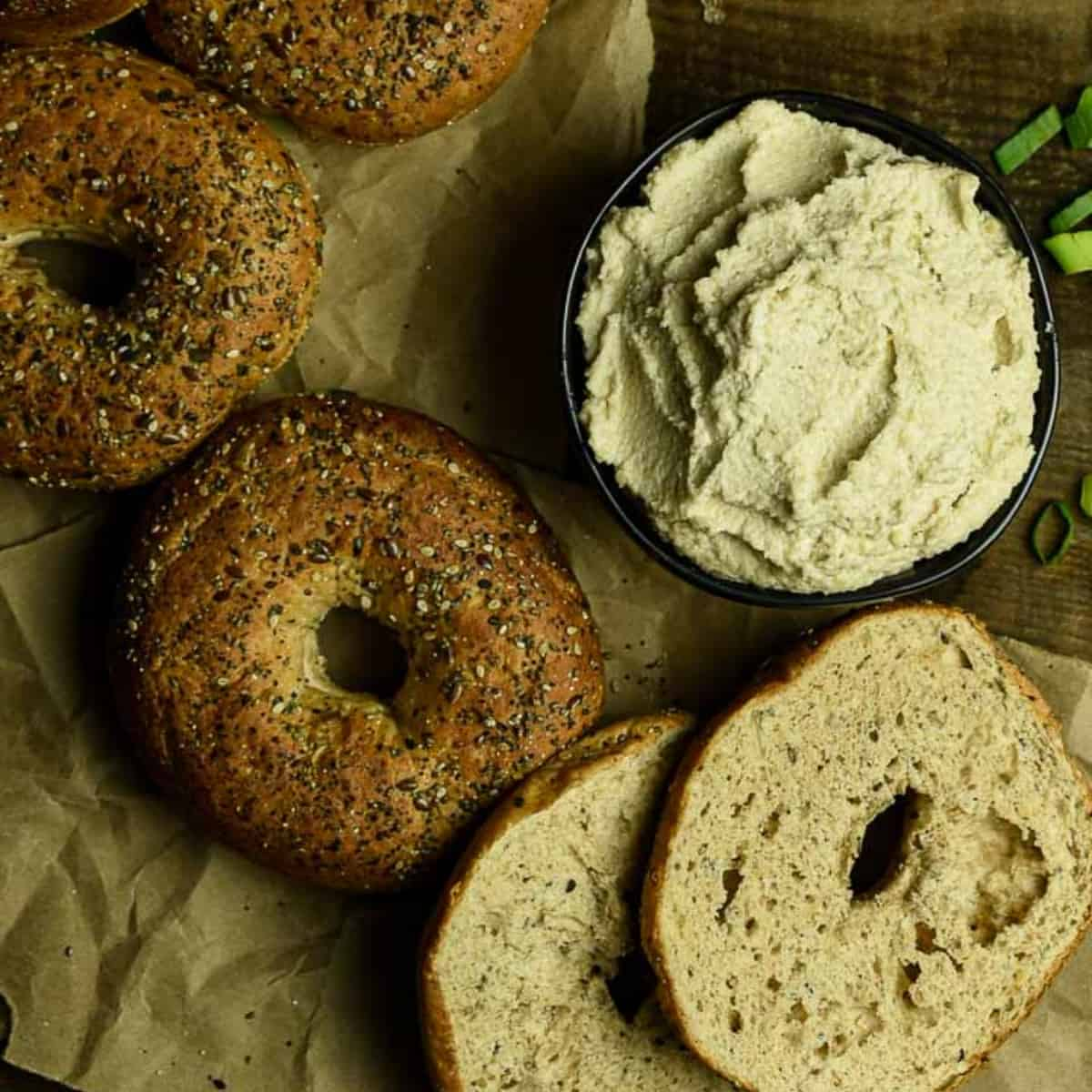 vegan cream cheese in bowl surrounded with bagles.