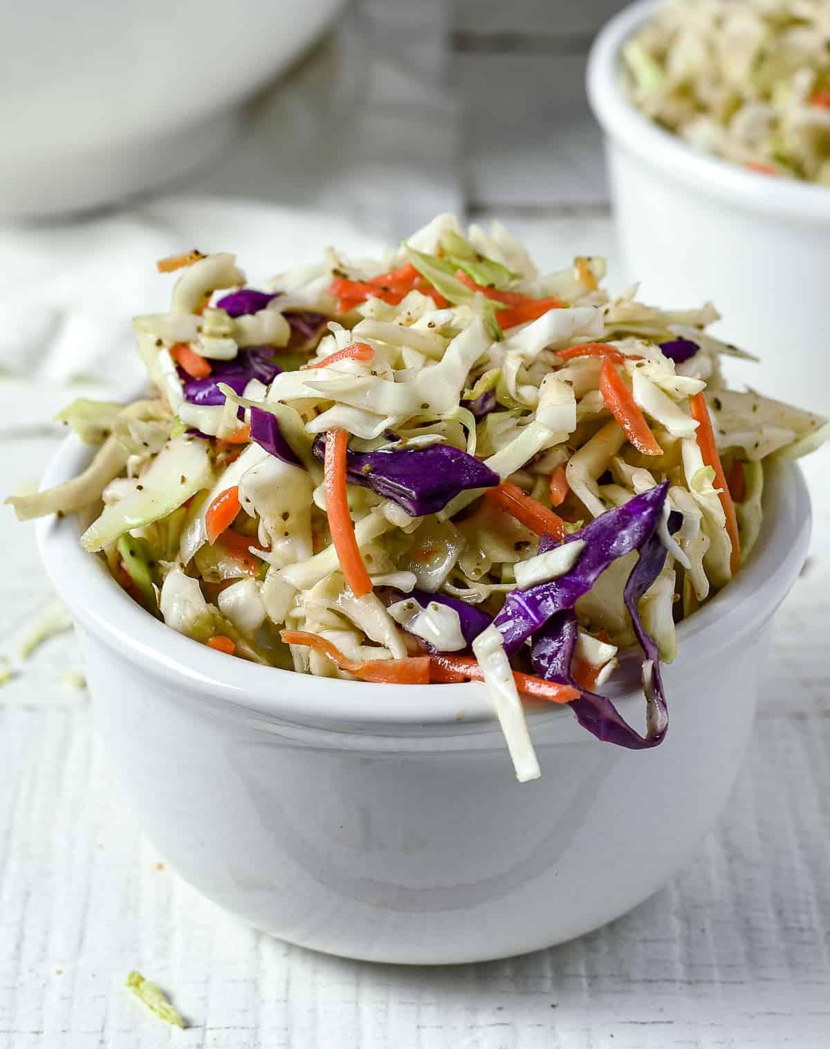 Vinegar coleslaw in white bowl.