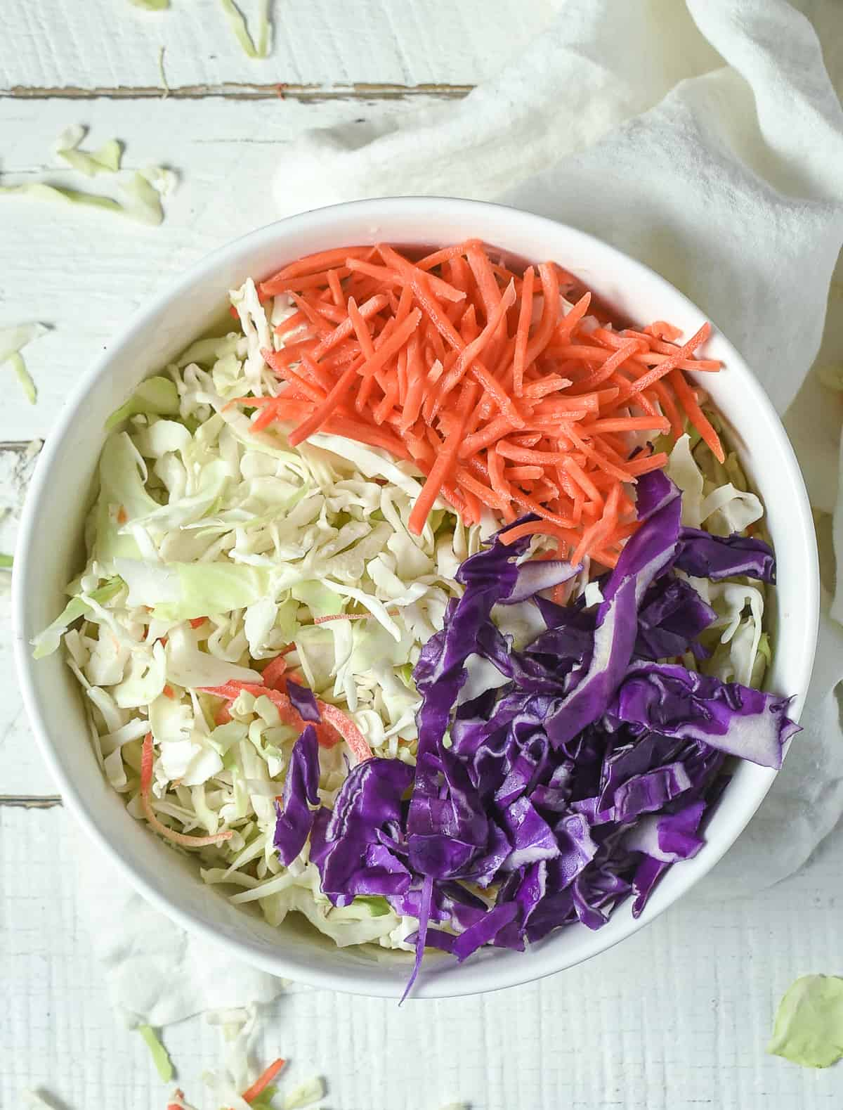 Green cabbage, red cabbage, and carrots in bowl.