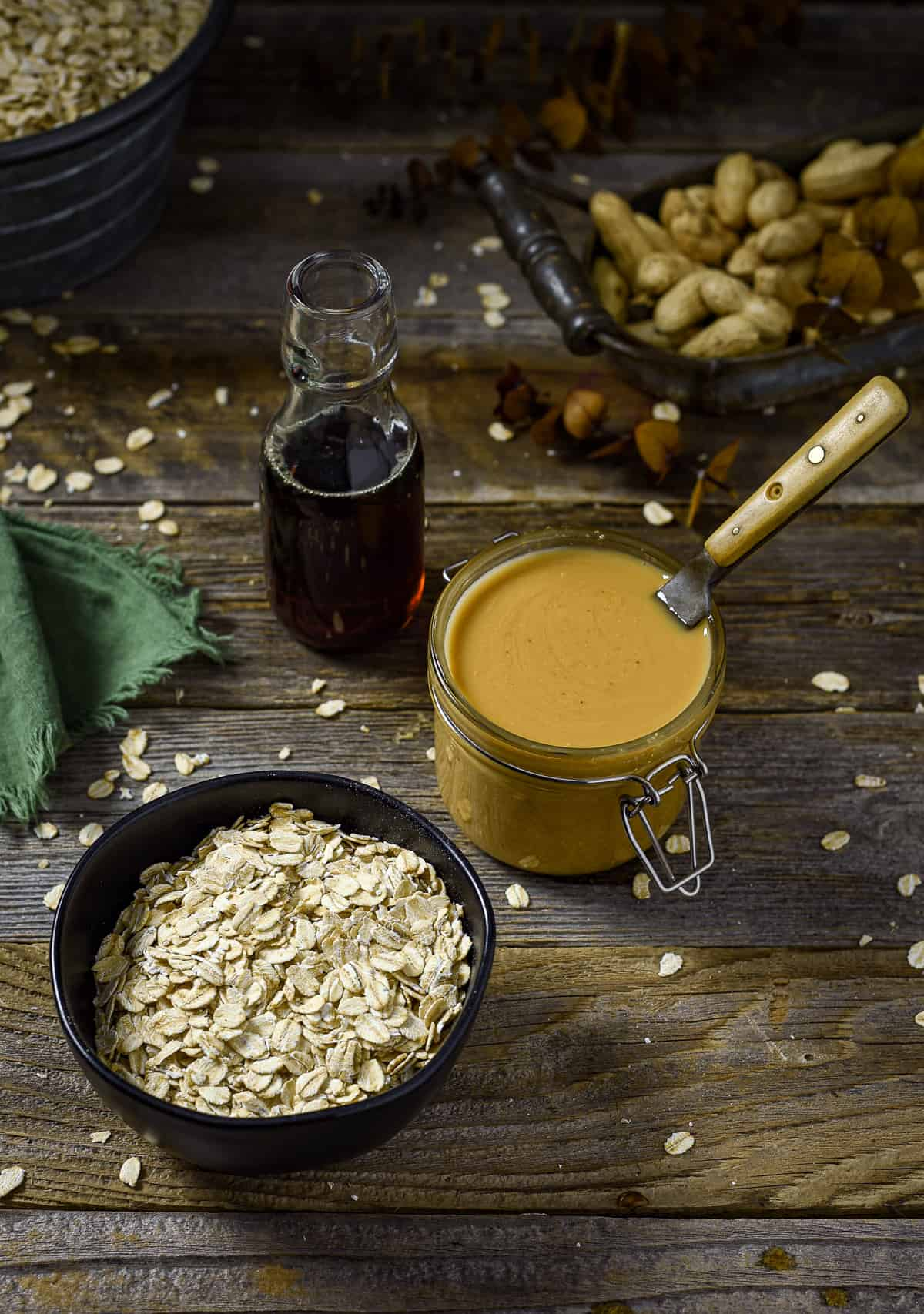 Oats, peanut butter, and maple syrup on table.