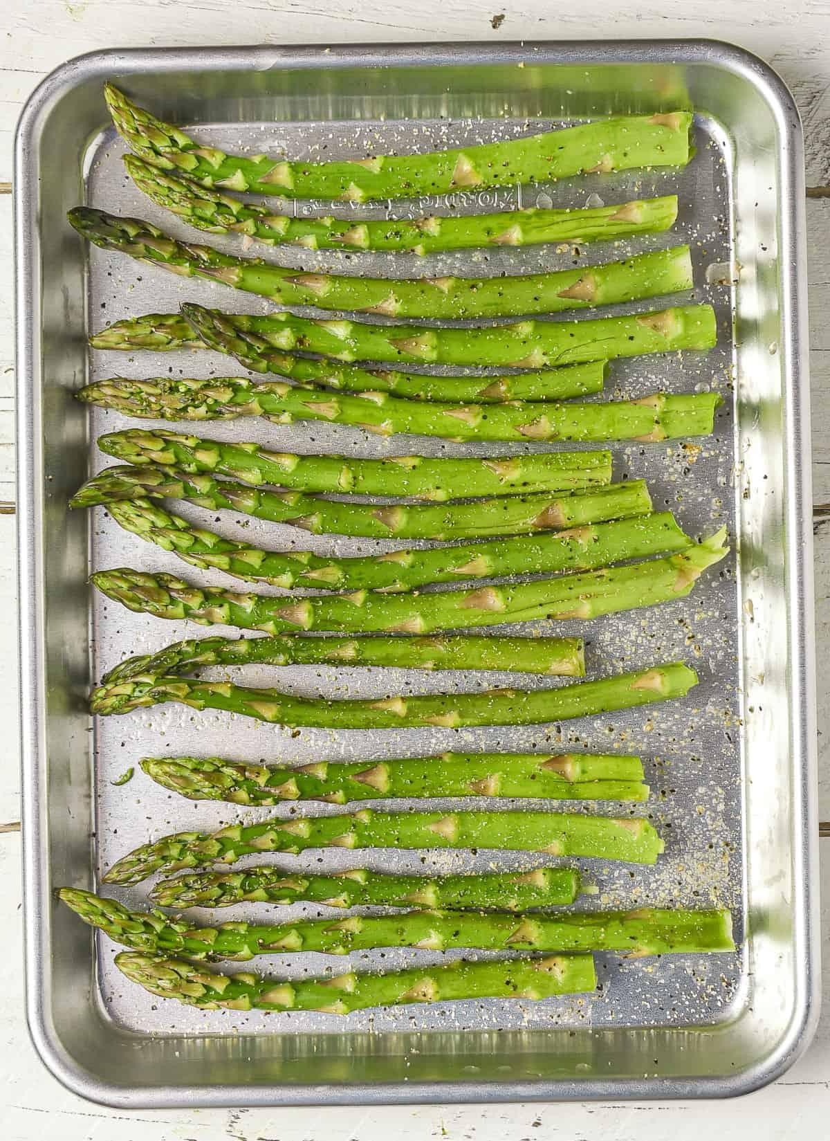 Seasoned asparagus on baking sheet.