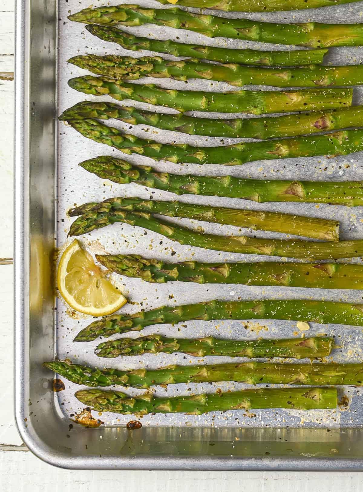 Roasted asparagus with lemon on baking sheet.