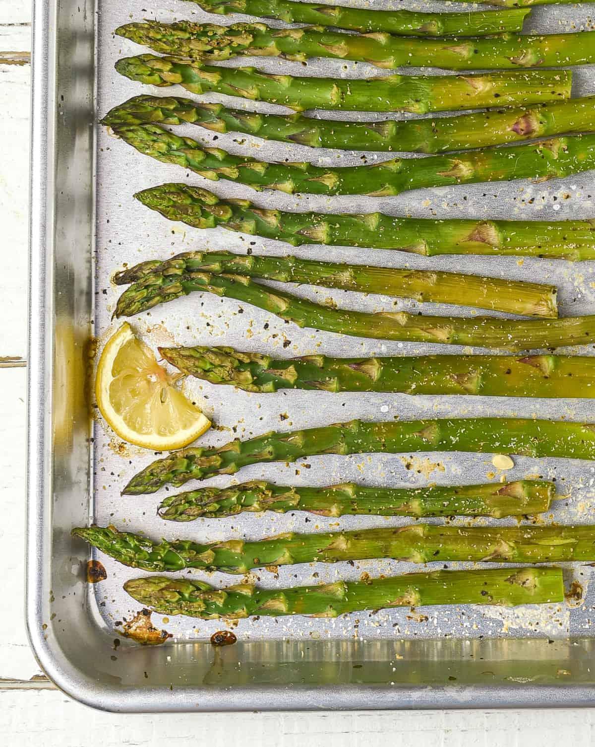 Easy roasted asparagus on baking sheet with lemon.