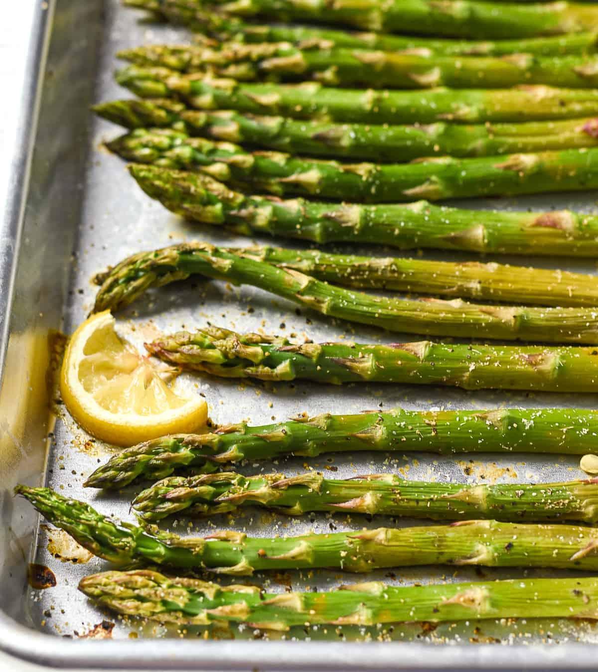 Roasted asparagus on baking sheet with lemon.