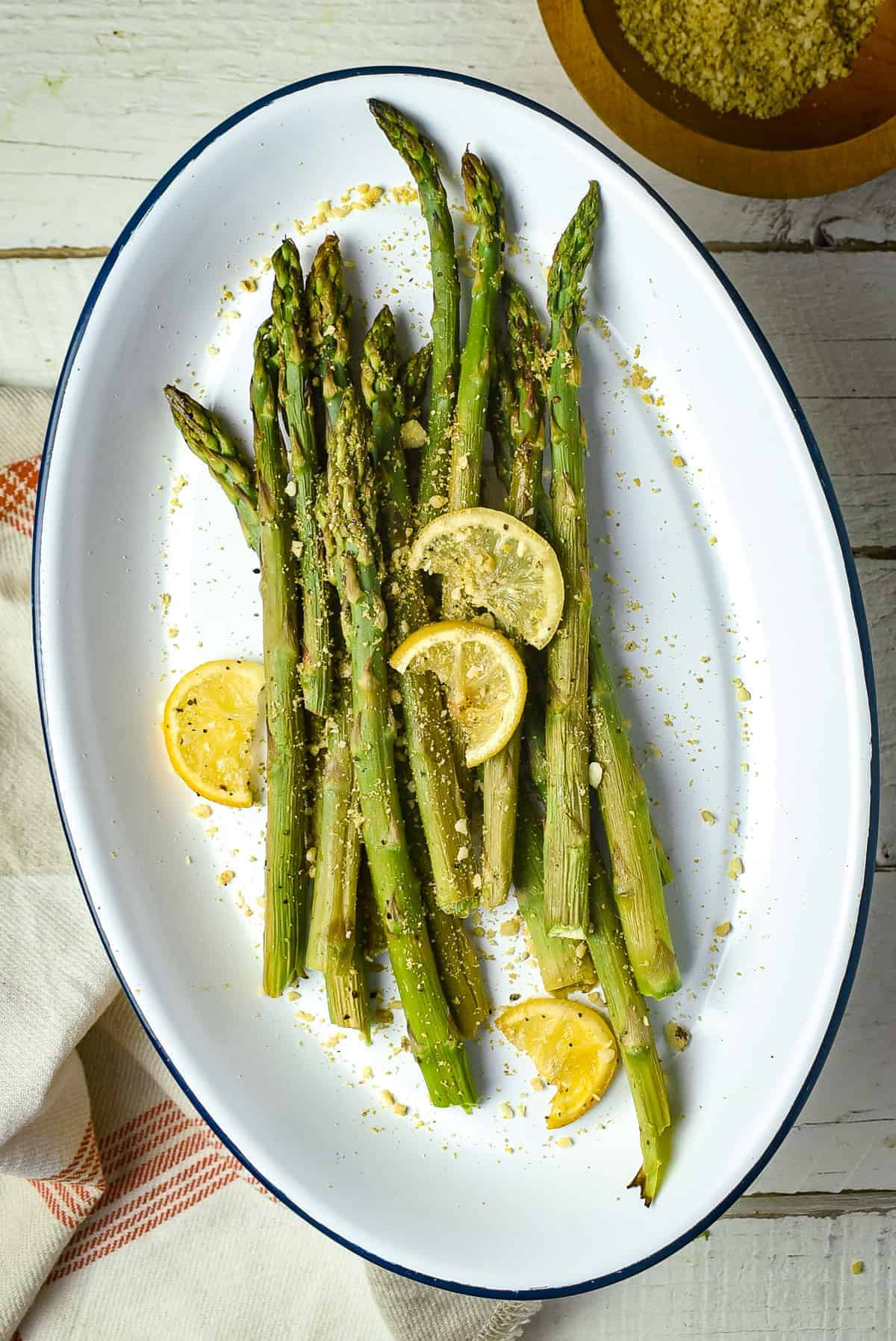 Easy roasted asparagus on platter with parmesan and lemon.