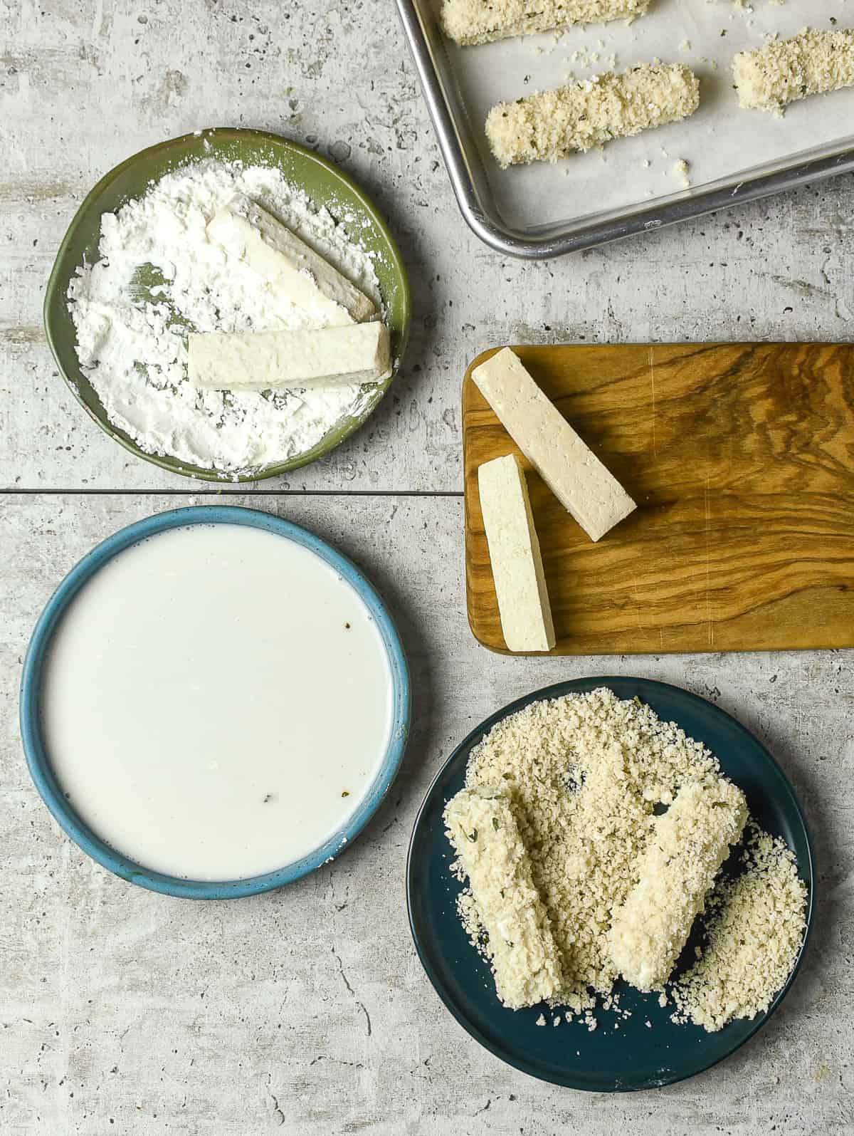 flour, milk, and bread crumbs in bowls with tofu on cutting board.