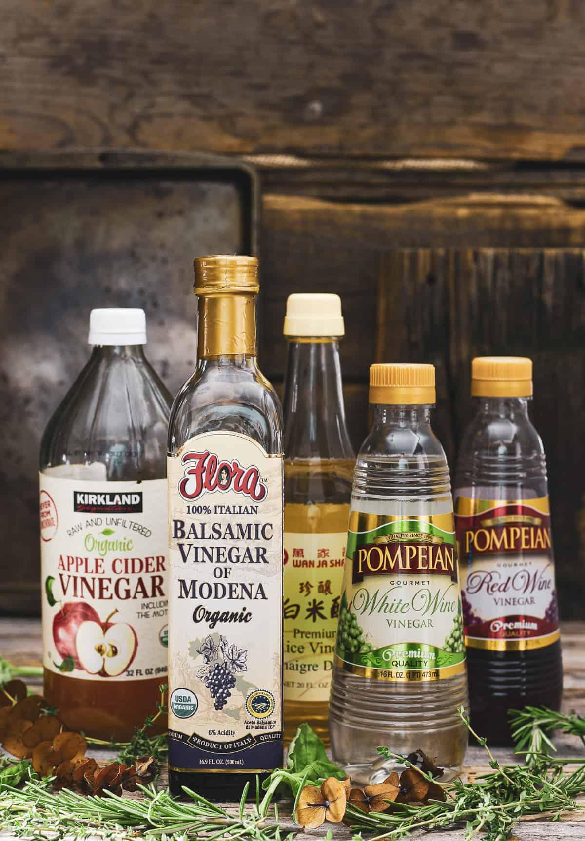 Five bottles of different types of vinegar.
