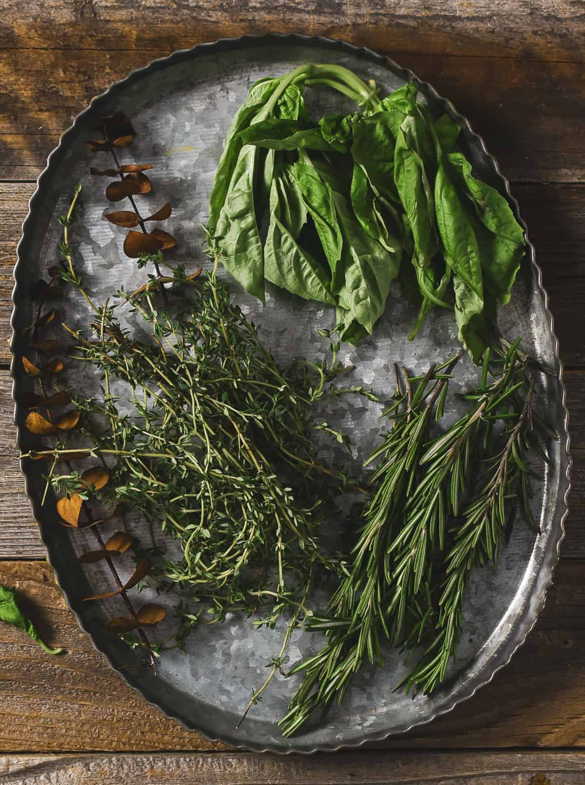 Fresh basil, thyme, and rosemary on tray.