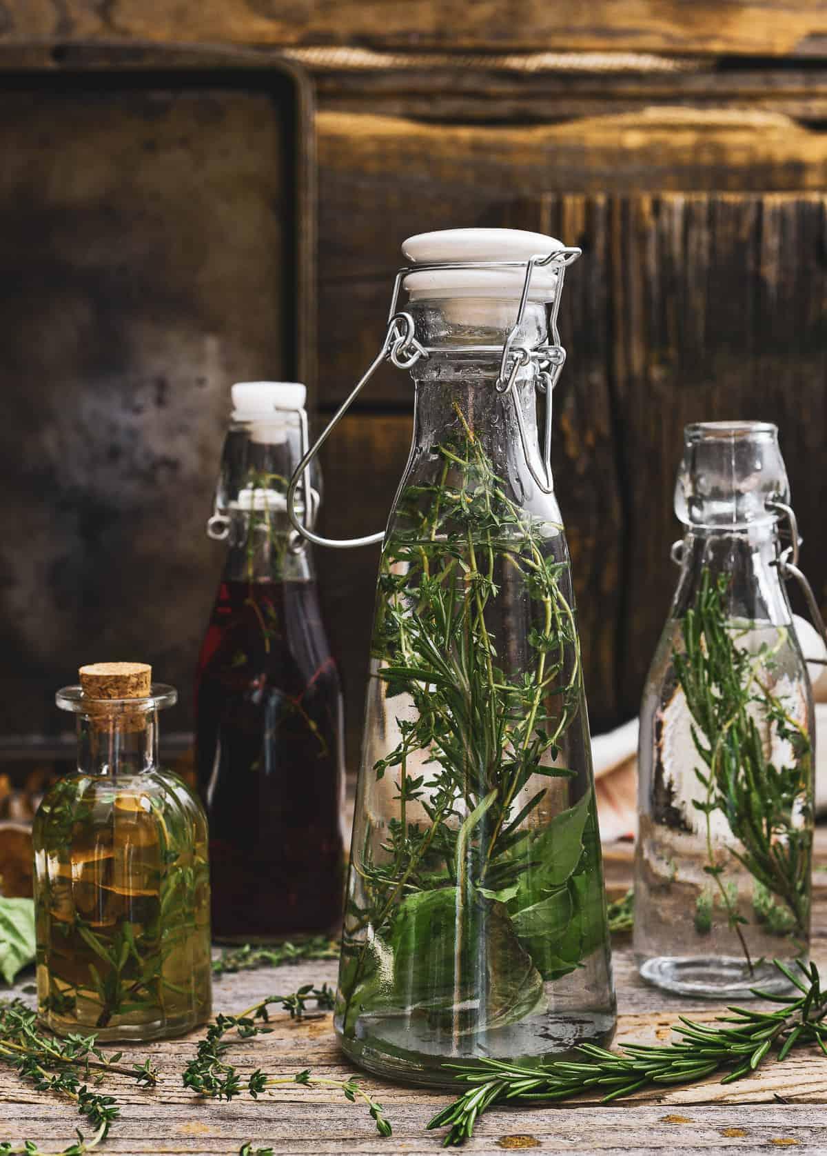 Four bottles of vinegar and herbs.