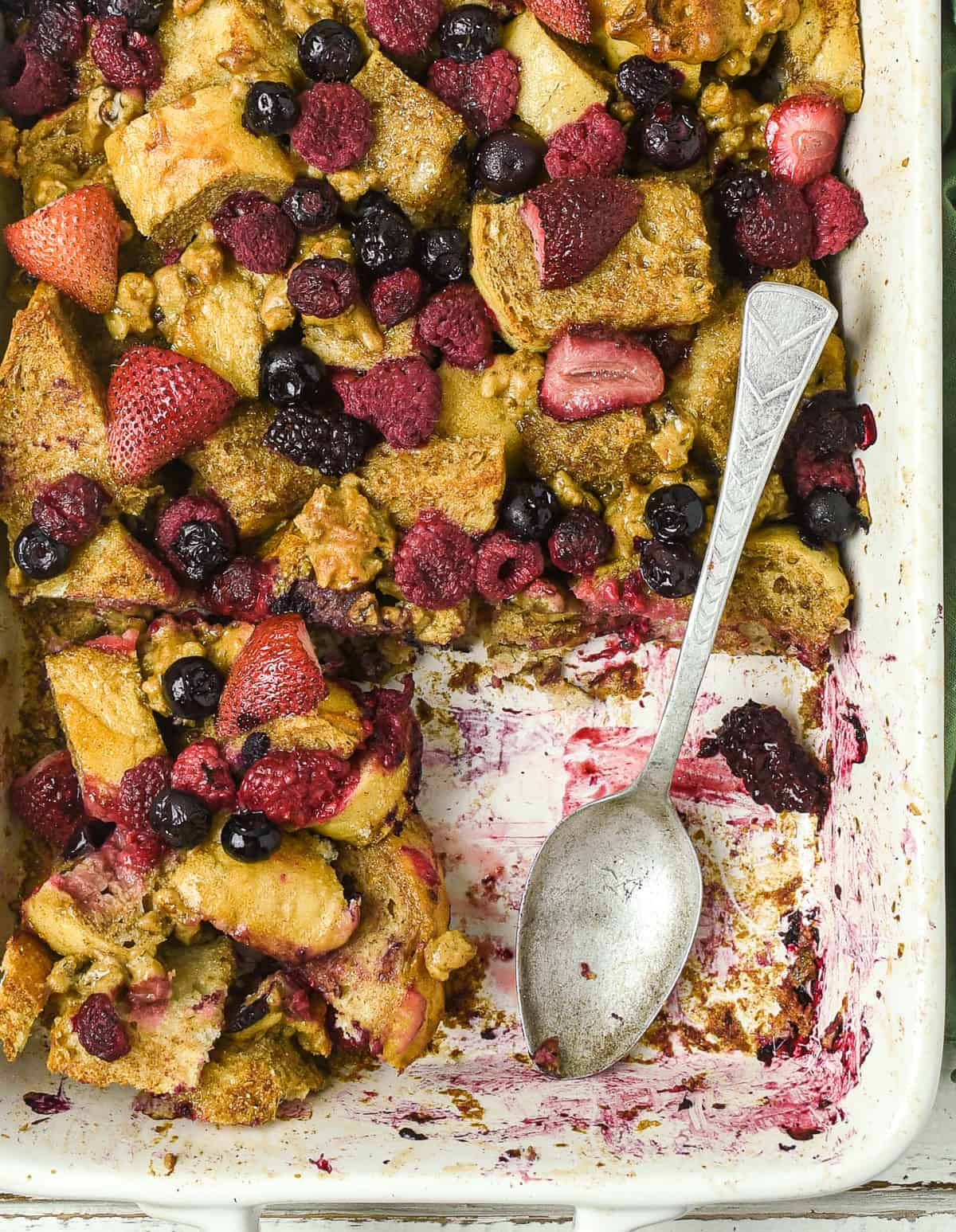 Spoon in baking dish with vegan french toast casserole.