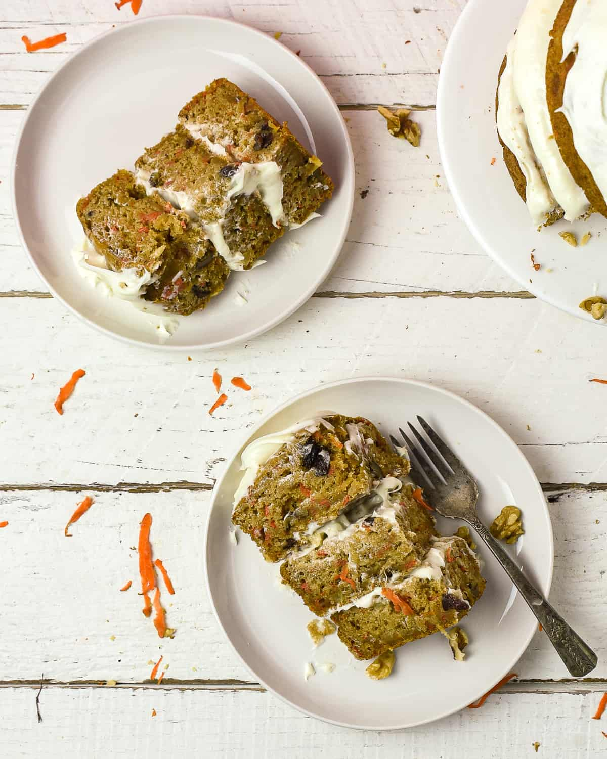 Two slices of vegan carrot cake on plates.