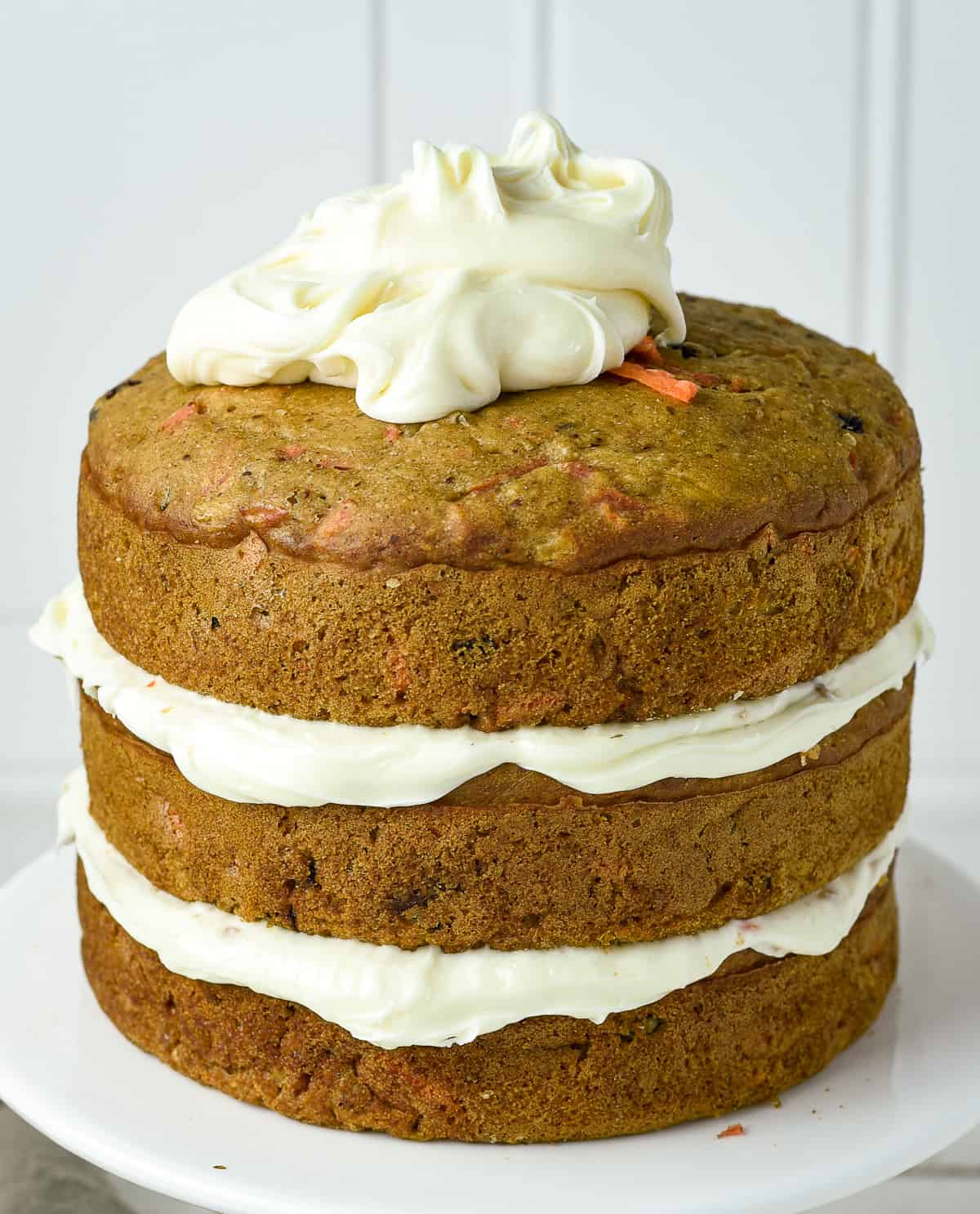 three layer carrot cake with dollop of frosting.