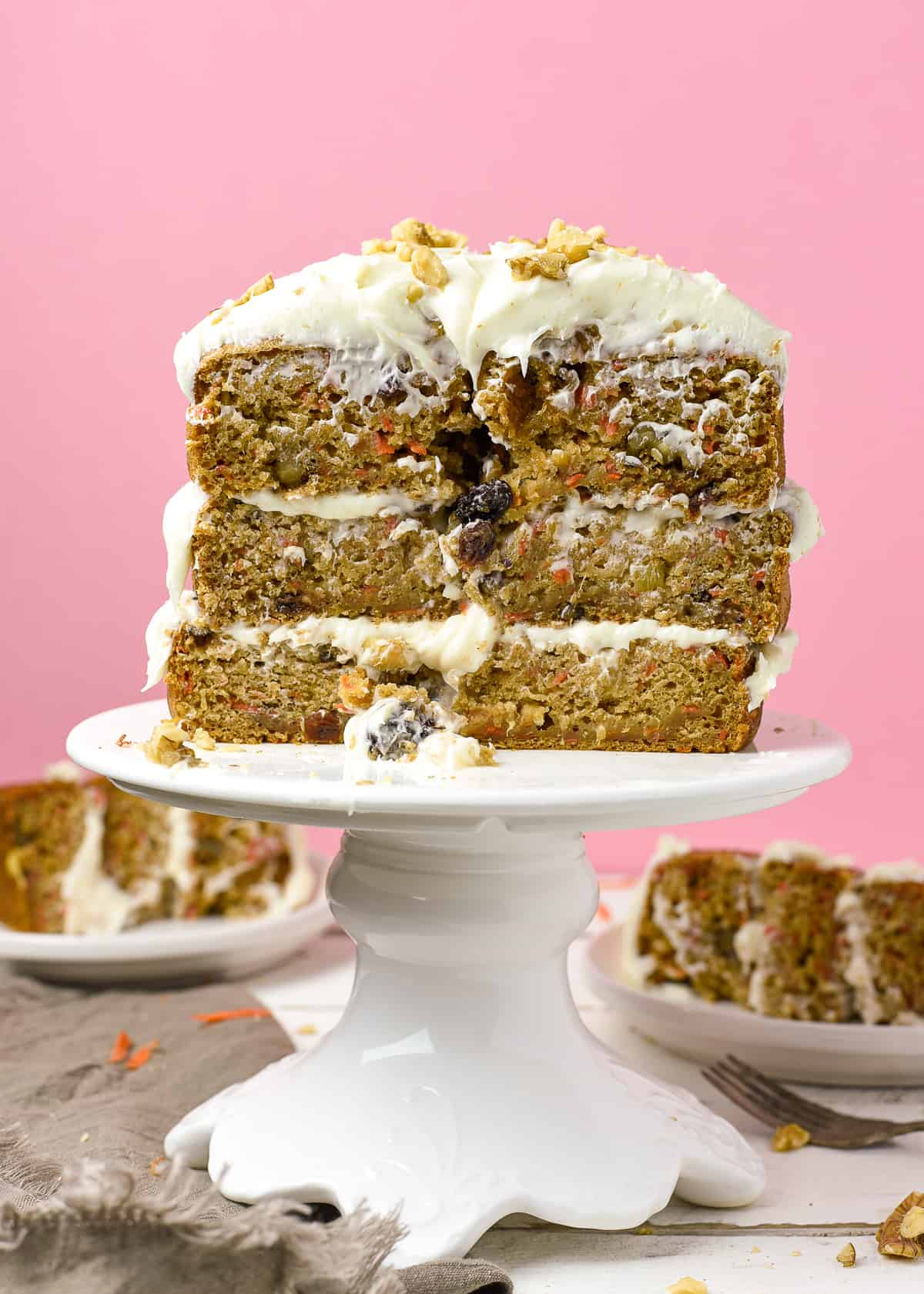 sliced vegan carrot cake on cake stand with a pink background