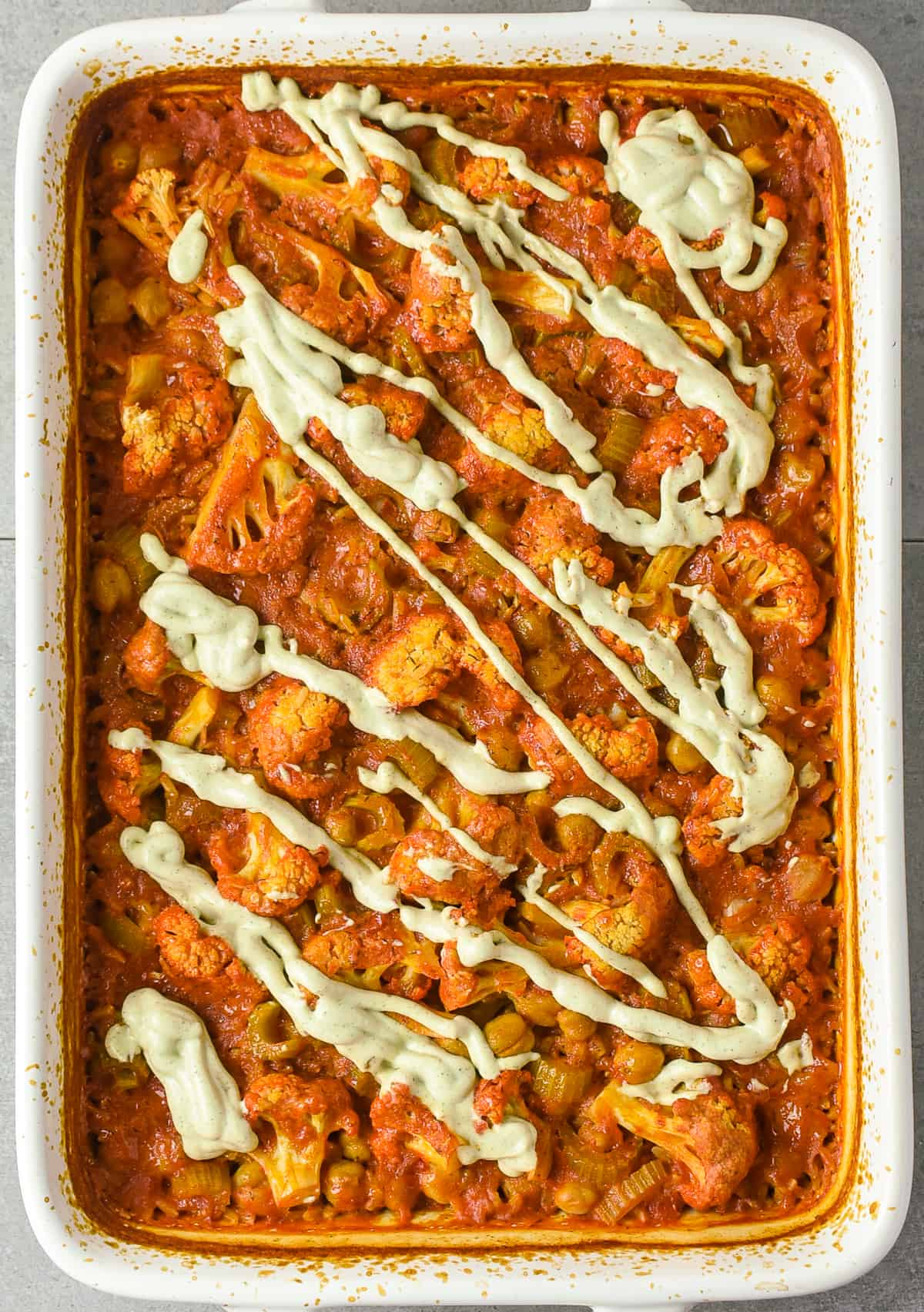 Buffalo chickpea cauliflower casserole topped with vegan ranch dressing.