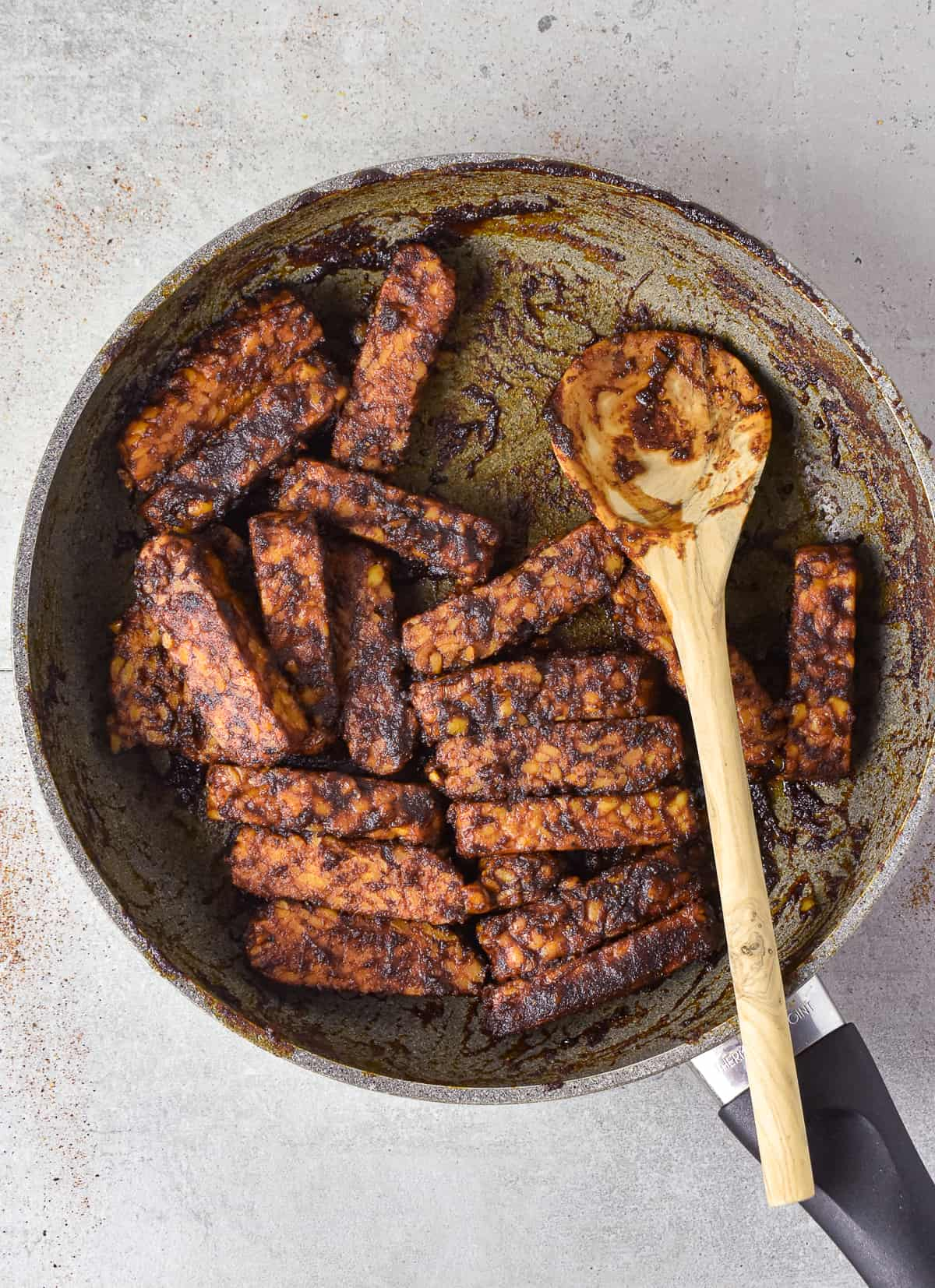 tempeh pieces in skillet and cooked with marinade.