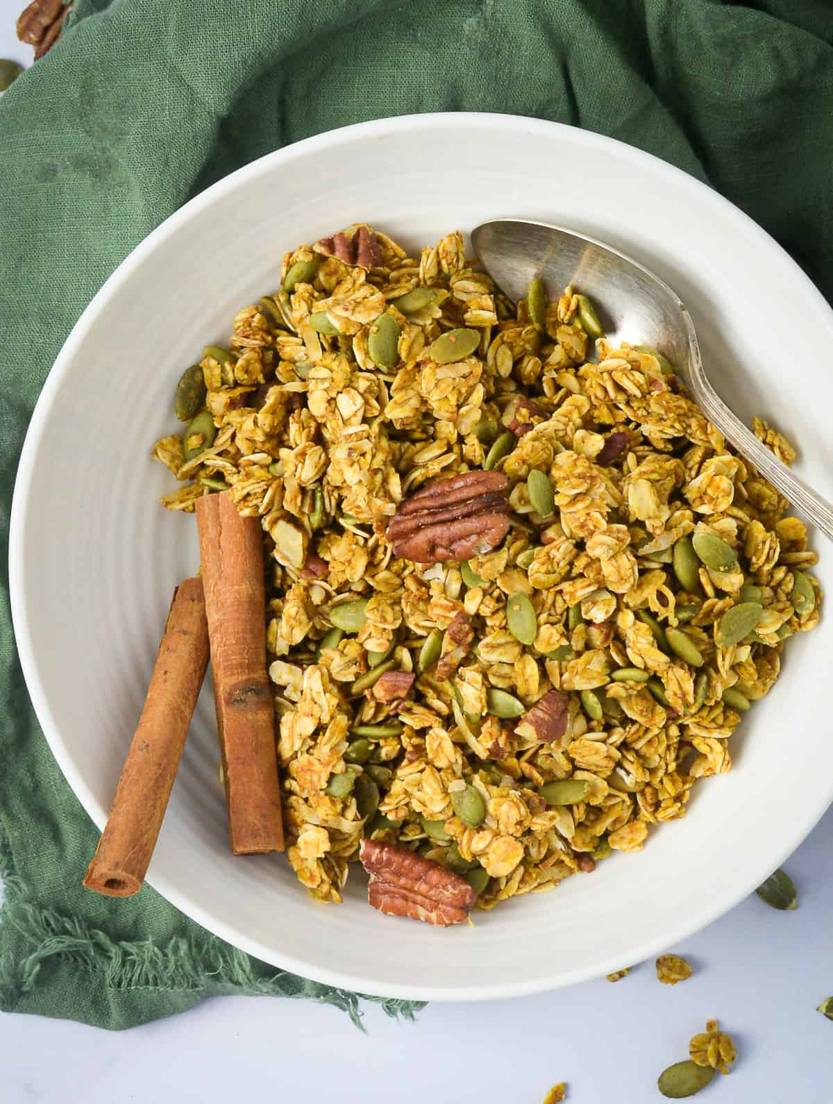 Vegan pumpkin granola in bowl with pecans and cinnamon sticks.